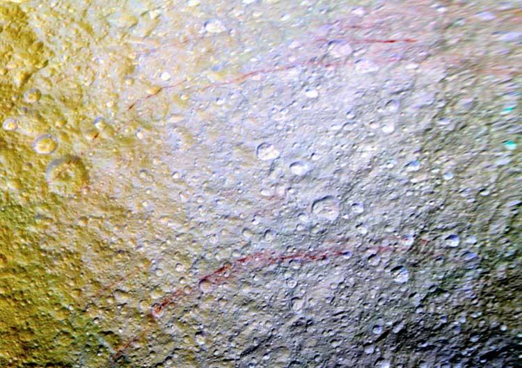 Renklendirilmiş görüntülerde Tetis yüzeyindeki kavisli kırmızı çizgiler (NASA/JPL-Caltech/Space Science Institute)