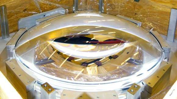 The C4 lens after it arrived at the NOAO. The faces of Gary Poczulp, Ron Probst, Dick Joyce and Ming Liang (project scientists for DESI) are reflected in the lens. Credit: Tim Miller/LBL Read more at: http://phys.org/news/2016-03-lenses-dark-energy.html#jCp