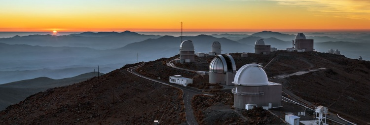 This majestic panorama gives context to ESO's La Silla Observatory. The site is positioned 2400 metres above sea level in the southern outskirts of Chile's Atacama Desert. Far from the light pollution of civilisation it provides a clear view of the night sky for ESO's telescopes. La Silla has been an ESO stronghold since the 1960s with only a selection of ESO's telescopes visible in this image: The ESO 1-metre Schmidt telescope, the ESO 1-metre telescope and the ESO 1.52-metre telescope are seen further towards the back. La Silla also hosts many national telescopes such as the Danish 1.54-metre telescope on the far left and the silver dome protecting the MPG/ESO 2.2-metre telescope. Fog is hovering over the valleys surrounding La Silla while the setting Sun leaves a layer of orange above the horizon. Once the Sun has disappeared the night sky will reveal impressive astronomical sights waiting to be observed.